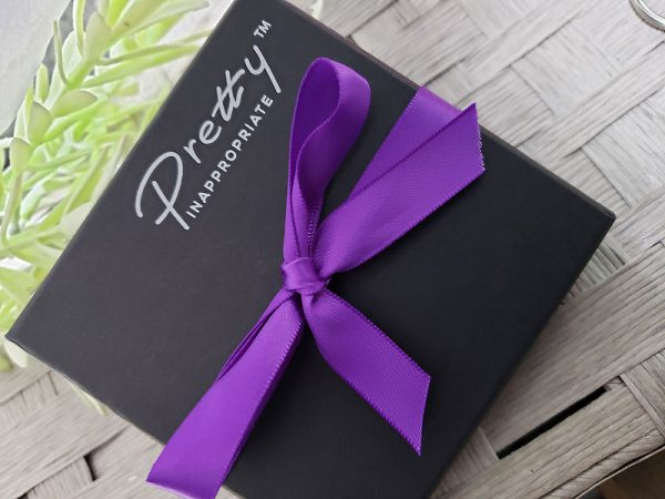 Box wrapped in purple ribbon with logo